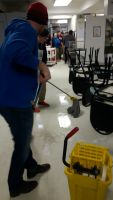 boys hockey team cleaning floors